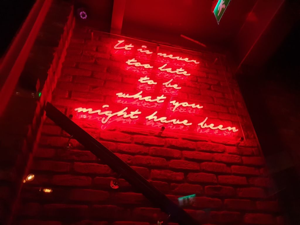 "Neon sign inside Marylebone pub says: ""It is never too late to be what you might have been""."
